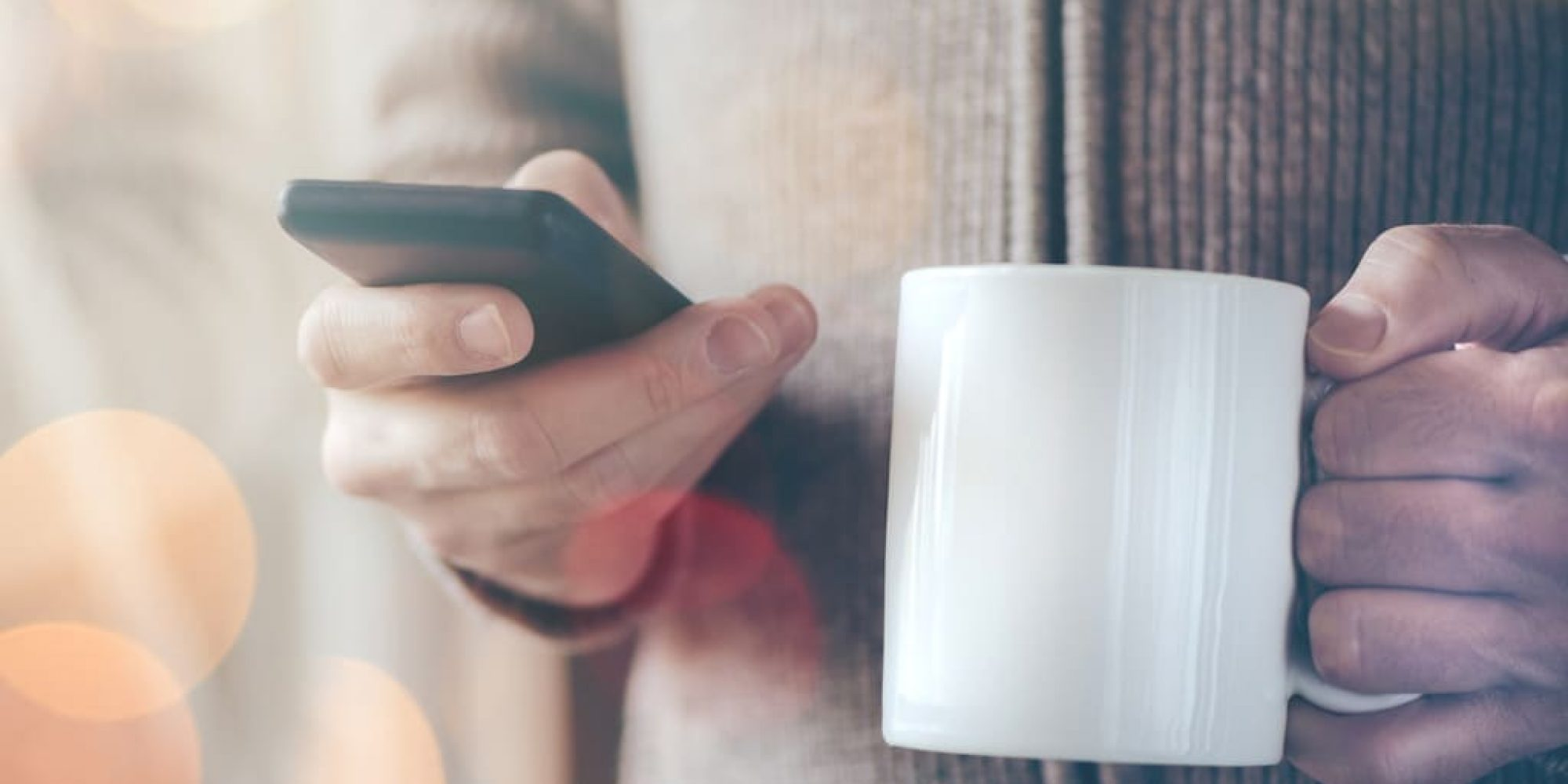 Casual man drinking coffee and reading text messages on smartphone, morning activity by the living room window, bokeh light and selective focus with shallow depth of field.